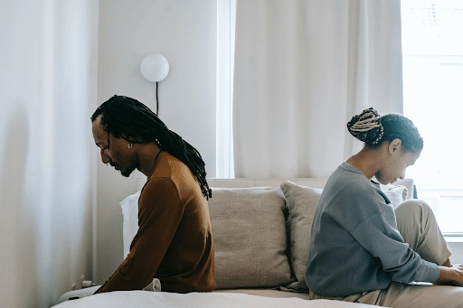 Black couple sitting opposite a bed with their backs on each other