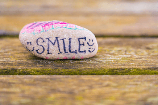 White and purple stone with the words SMILE written on it