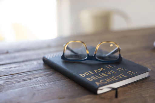Black and brown glasses on top of a black notebook with the words 'Dream it. Believe it. Achieve it.' written on its cover'