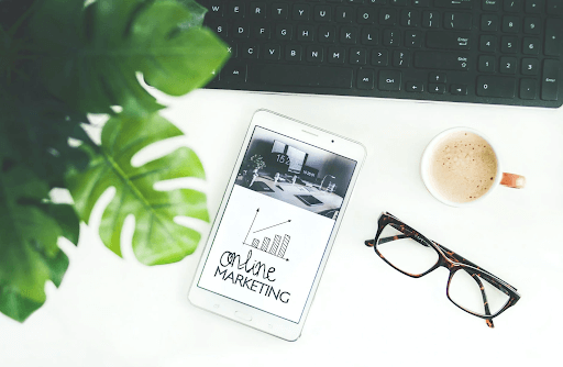 """An eyeglass, coffee cup, and a phone with """"online marketing"""" on its screen"""