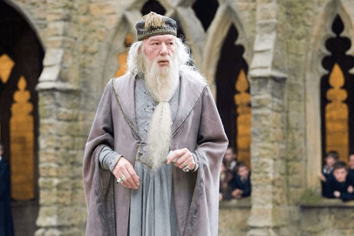 Dumbledore standing and surrounded by Hogwarts students