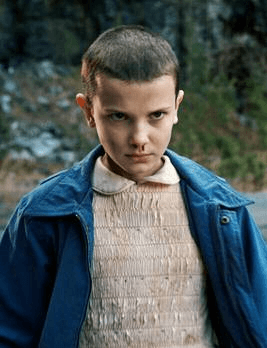 Eleven with nose bleed wearing an old dress and blue jacket