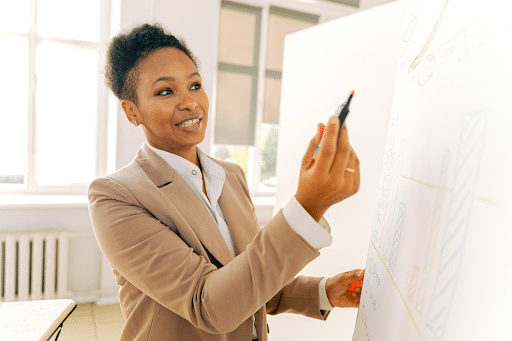 A businesswoman in a beige suit holding a highlighter in front of a whiteboard