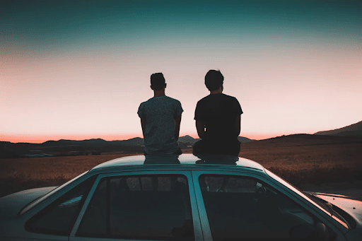 Two men seating on a vehicle parked on a road near a brown grass field