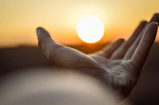 A man's hand that seems to be holding the rising sun on his palms