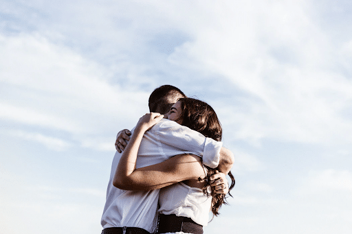 hugging couple with sky background