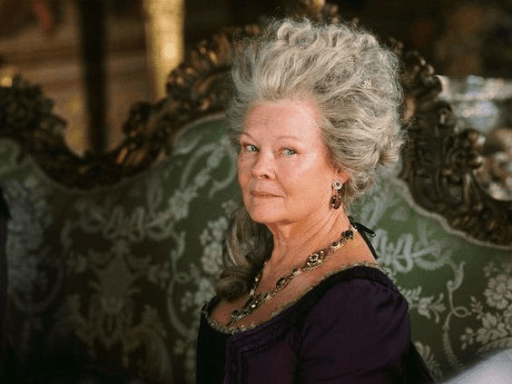 Lady Catherine de Bourgh wearing a purple dress sitting on a green sofa designed with white flowers