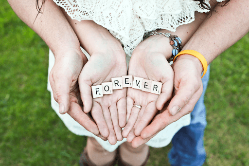 A couple holding forever scrabble letters