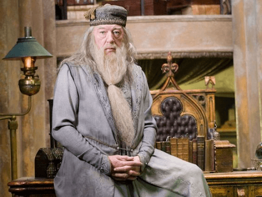 Dumbledore sitting on his table with fingers intertwined