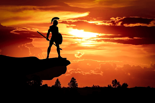 Silhouette of a Spartan warrior holding a shield and a spear at sun dusk
