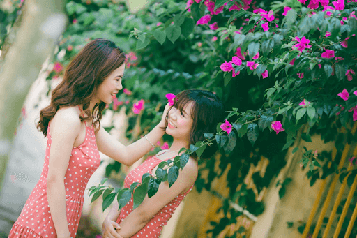 Two young women in dotted, sleeveless shirts beside flowers and smiling at each other