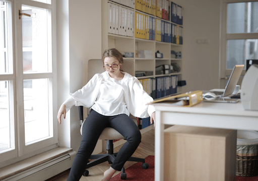 Arrogant woman in a white top and black pants sitting in an office