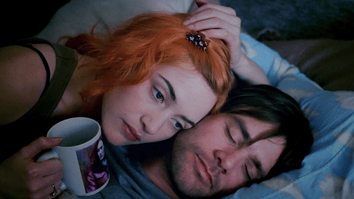 Clementine and Joel in a bed, with Clementine holding a cup