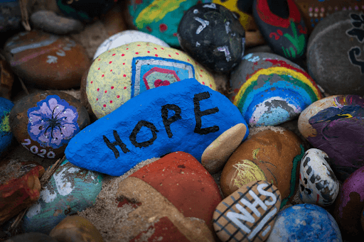 Painted rocks with 'HOPE' written on the blue rock in the middle