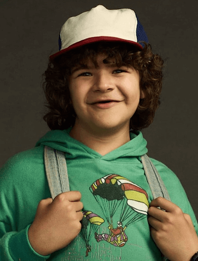 Dustin smiling and holding unto his backpack