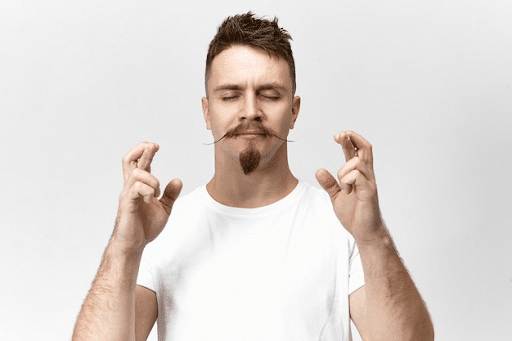 Young bearded hipster guy with closed eyes and crossed fingers while wishing for good luck