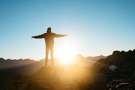 Silhouette of a person standing on a hill during sunrise