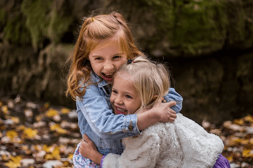 two sisters hugging each other and smiling