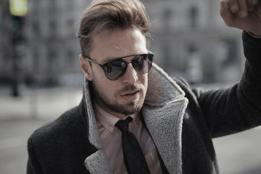 confident and classy man wearing preppy clothes and sunglasses in a city street