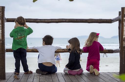 Four kids on a deck near a beach