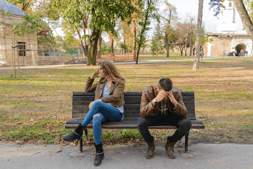 Woman and a man with hands on his head sitting on a brown wooden bench