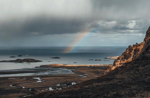 End of a rainbow on an ocean on a cloudy day
