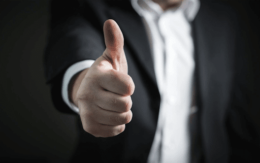 Close-up of a thumbs up hand of a man in a suit