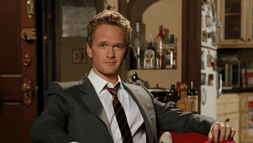 Barney Stinson in a suit with a slight smirk