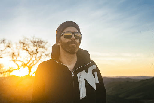 cool man wearing sunglasses and a hoodie looking off into the distance on a mountain overlooking a hill landscape at sunset