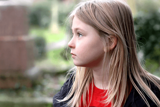 Side face photo of a blonde young girl looking to the left