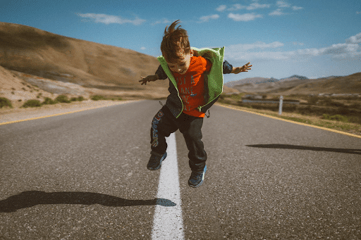 A little boy jumping on a concrete road in a barren place