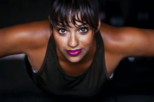 Smiling woman in a black tank top with arms spread out