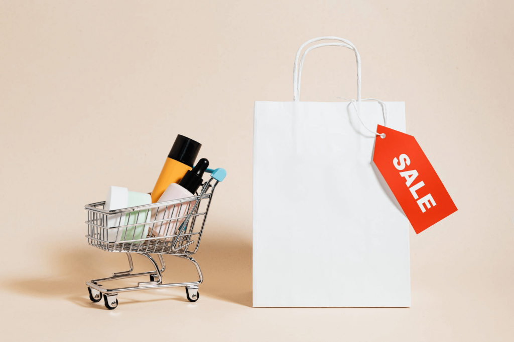 """white paper bag with a red """"SALE"""" tag, and a small pushcart with cosmetics in it"""