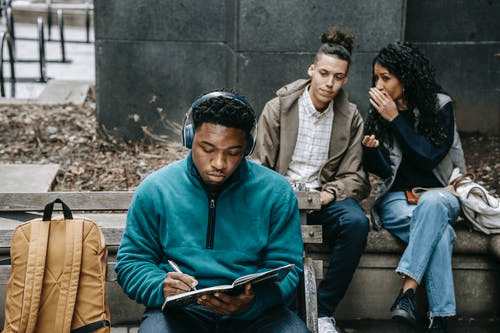 Multiracial Students Gossiping about Black Man with Notepad