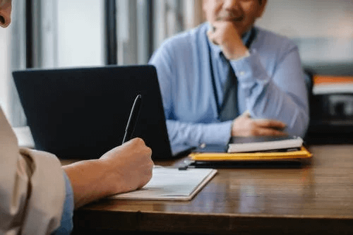 Woman Filing job Application Form in Office with Boss
