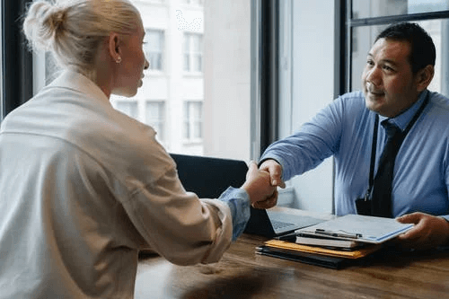 Businessman Shaking Hand of Applicant in Office