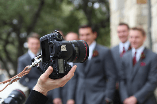 Hand of a man in a black suit wearing a digital camera