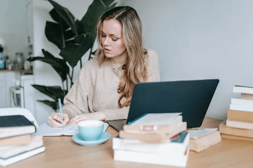 Businesswoman Writing Information on Notebook with Laptop and Coffee