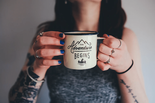 """A woman holding a mug with a """"The adventure begins"""" print"""