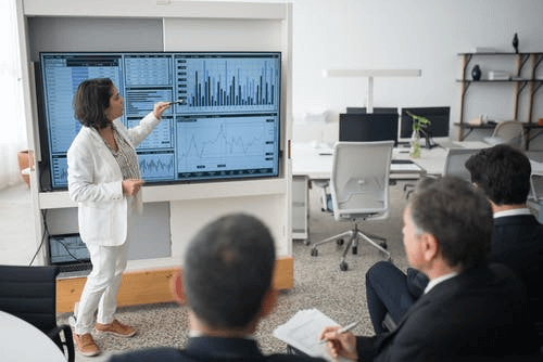 Woman in White Suit Discussing Stock Market Data to Her Colleague