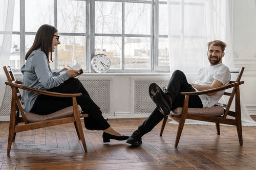 Woman Sitting on Brown Chair talking with a man