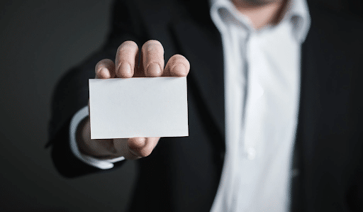 A man in a back suit holding a white business card