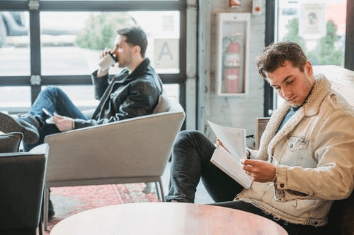 Young Entrepreneurs Working with Papers Drinking Coffee in Cafe