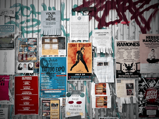 Assorted posters posted on a grey wall