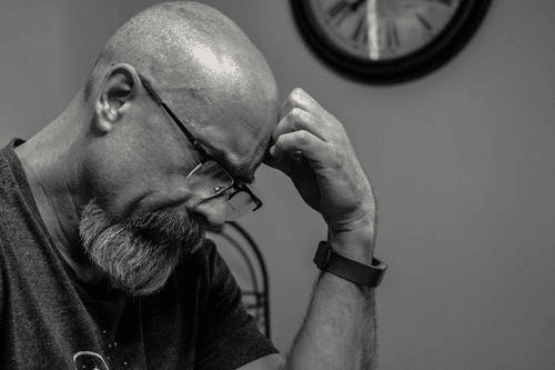 Grayscale Photo of Man Thinking In Front of Analog Clock