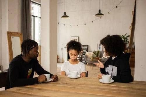 Black Parents Lecturing Upset Daughter at Table